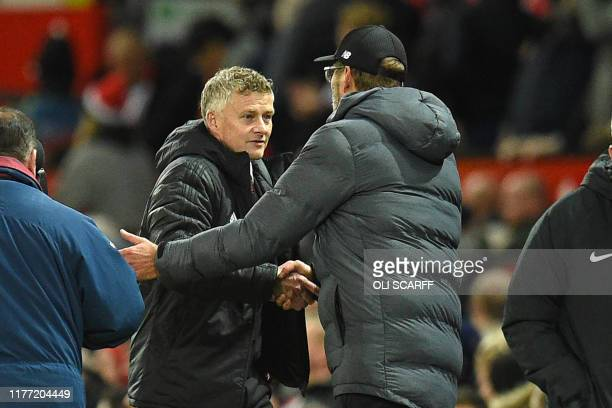Manchester United's Norwegian manager Ole Gunnar Solskjaer and Liverpool's German manager Jurgen Klopp shake hands after the English Premier League...