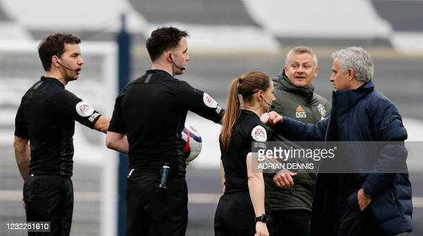 Manchester United's Norwegian manager Ole Gunnar Solskjaer and Tottenham Hotspur's Portuguese head coach Jose Mourinho hit fists with the referees...