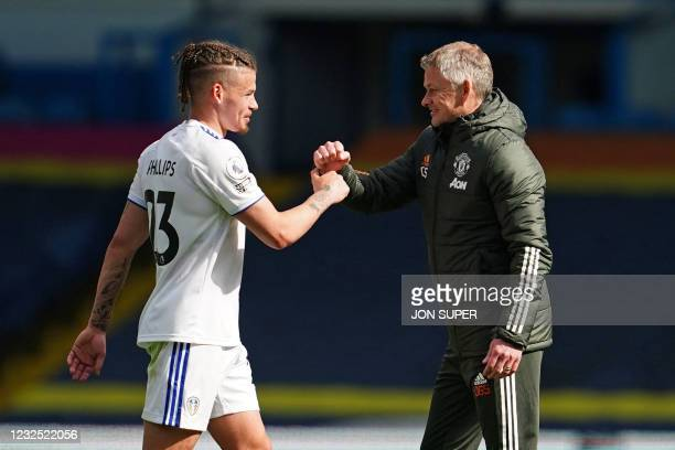 Manchester United's Norwegian manager Ole Gunnar Solskjaer and Leeds United's English midfielder Kalvin Phillips bump fists after the English Premier...