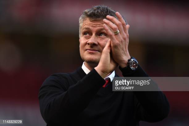 Manchester United's Norwegian manager Ole Gunnar Solskjaer applauds supporters on the pitch after the English Premier League football match between...