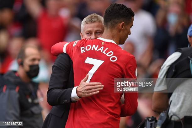 Manchester United's Norwegian manager Ole Gunnar Solskjaer embraces Manchester United's Portuguese striker Cristiano Ronaldo after the English...