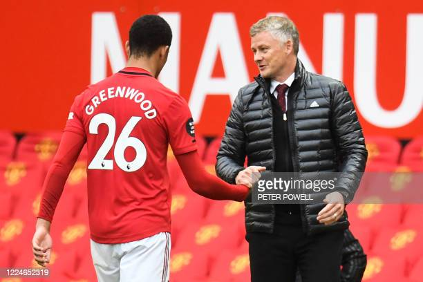 Manchester United's Norwegian manager Ole Gunnar Solskjaer congratulates Manchester United's English striker Mason Greenwood (L0 as he leavs the...