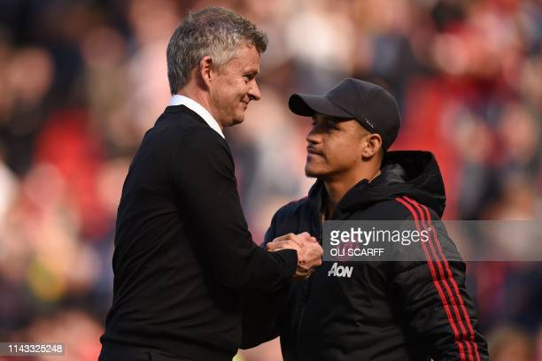 Manchester United's Norwegian manager Ole Gunnar Solskjaer shakes hands with Manchester United's Chilean striker Alexis Sanchez on the pitch after...