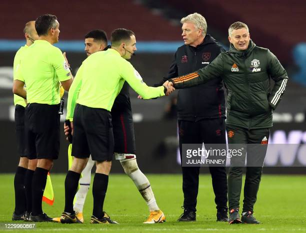 Manchester United's Norwegian manager Ole Gunnar Solskjaer shakes hands with the assistant referee as West Ham United's Scottish manager David Moyes...