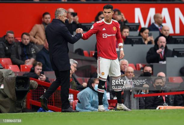 Manchester United's Norwegian manager Ole Gunnar Solskjaer shakes hands with Manchester United's Portuguese striker Cristiano Ronaldo as he comes off...