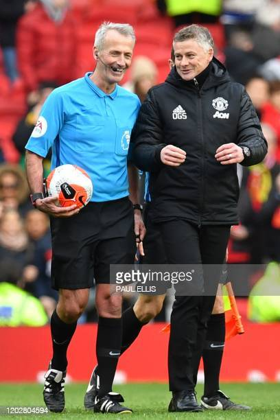 Manchester United's Norwegian manager Ole Gunnar Solskjaer talks with referee Martin Atkinson at the end of the English Premier League football match...