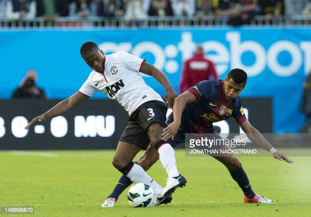 Manchester United's Patrice Evra vies with Barcelona's Alexis Sanchez during the friendly football match between Barcelona FC and Manchester United...