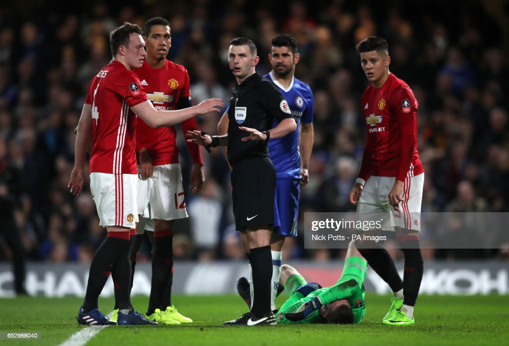 Manchester United's Phil Jones (left) speaks to referee Michael Oliver as Manchester United goalkeeper David De Gea lays injured during the Emirates FA Cup, Quarter Final match at Stamford Bridge, London.