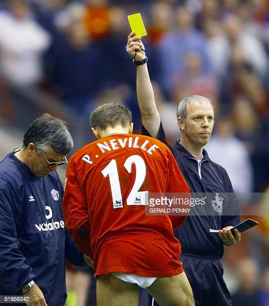 Manchester United's Phil Neville is shown the yellow card as he changes his shorts during their Premiership match against Derby County 05 May 2001 at...