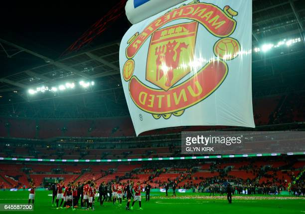 Manchester United's players celebrate on the pitch after their victory in the English League Cup final football match between Manchester United and...