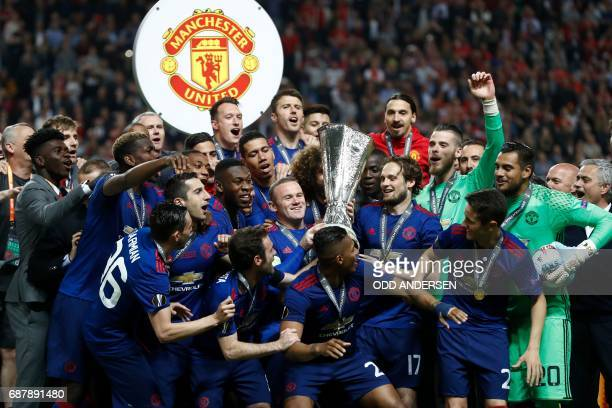 TOPSHOT Manchester United's players including English striker Wayne Rooney celebrate with the trophy after the UEFA Europa League final football...