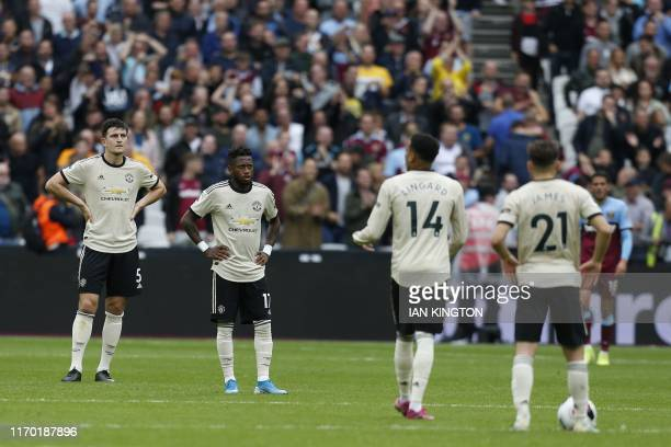 Manchester United's players react after West Ham United's English defender Aaron Cresswell scores his team's second goal during the English Premier...