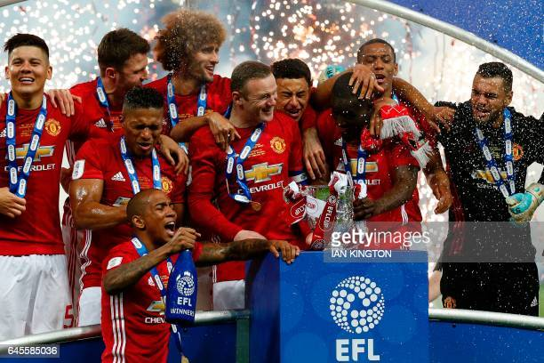 TOPSHOT Manchester United's players spray champagne as they celebrate with the trophy on the pitch after their victory in the English League Cup...