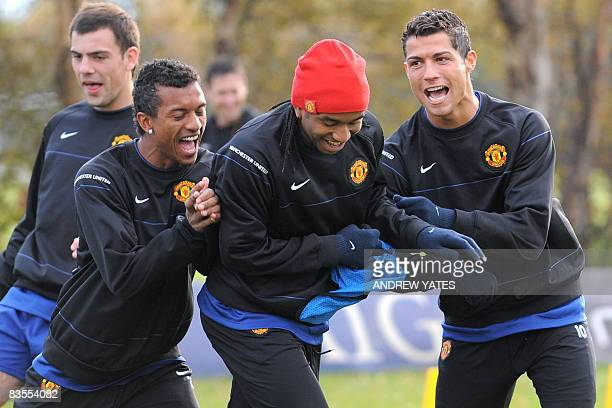 Manchester United's Portugese midfielder Cristiano Ronaldo Brazilian midfielder Anderson and Portugese midfielder Nani laugh during a training...