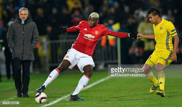 Manchester United's Portuguese coach Jose Mourinho looks at Manchester United's French midfielder Paul Pogba fighting for the ball with Rostov's...