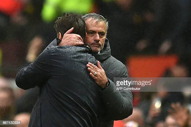 Manchester United's Portuguese manager Jose Mourinho and Tottenham Hotspur's Argentinian head coach Mauricio Pochettino embrace after the English...