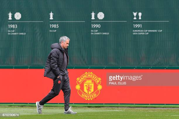 Manchester United's Portuguese manager Jose Mourinho arrives on the pitch for a training session at the club's training complex near Carrington, west...