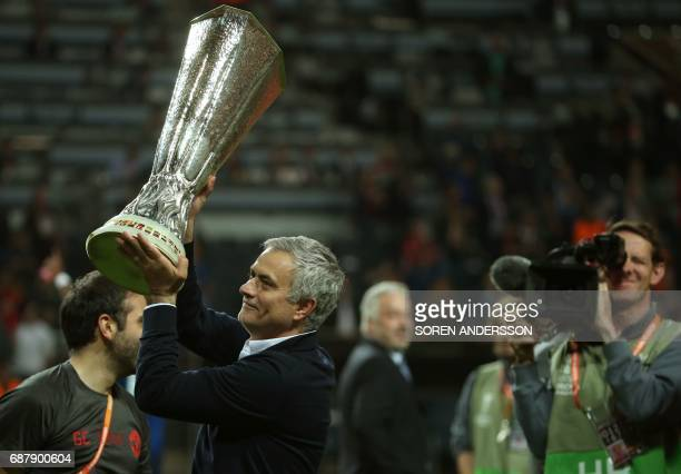 Manchester United's Portuguese manager Jose Mourinho celebrates with the trophy after his team won the UEFA Europa League final football match Ajax...