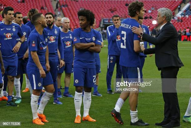 Manchester United's Portuguese manager Jose Mourinho congratulates Chelsea players as they celebrate their win after the English FA Cup final...