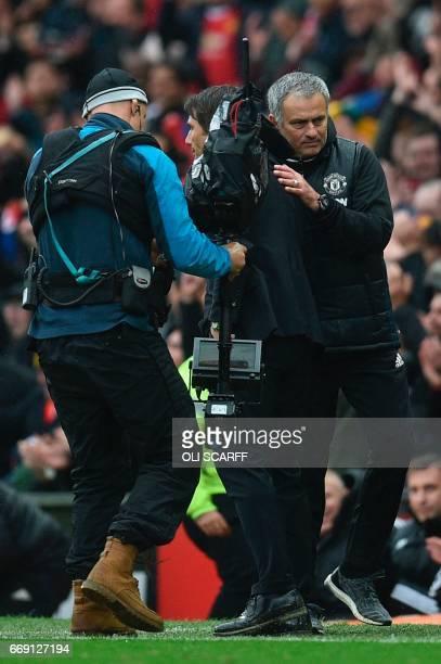Manchester United's Portuguese manager Jose Mourinho embraces Chelsea's Italian head coach Antonio Conte at the end of the English Premier League...