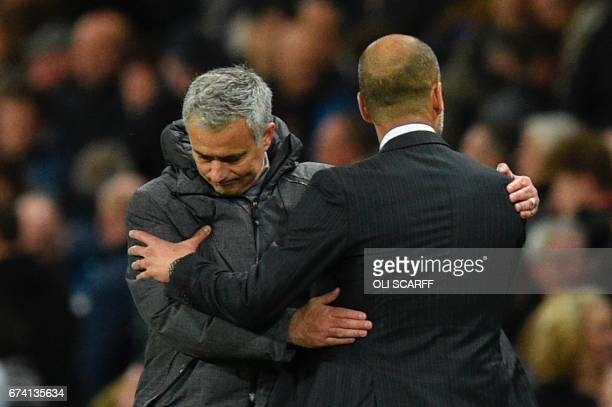 Manchester United's Portuguese manager Jose Mourinho embraces Manchester City's Spanish manager Pep Guardiola on the touchline at the end of the...