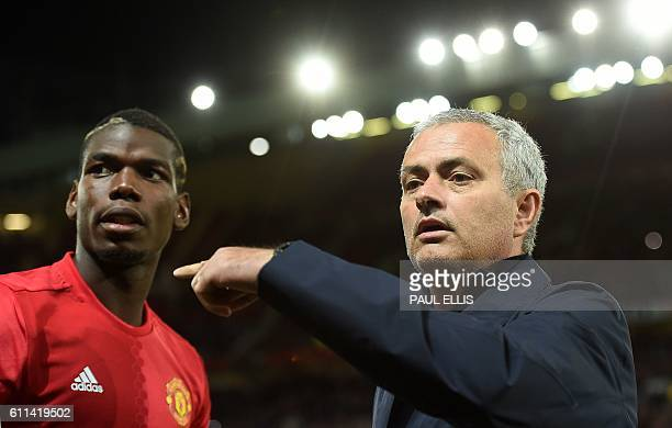 Manchester United's Portuguese manager Jose Mourinho gestures to Manchester United's French midfielder Paul Pogba as he arrives on the pitch ahead of...