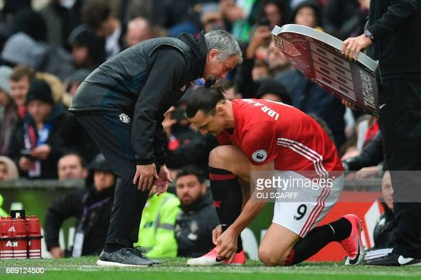 Manchester United's Portuguese manager Jose Mourinho gives substitute Manchester United's Swedish striker Zlatan Ibrahimovic instructions before his...