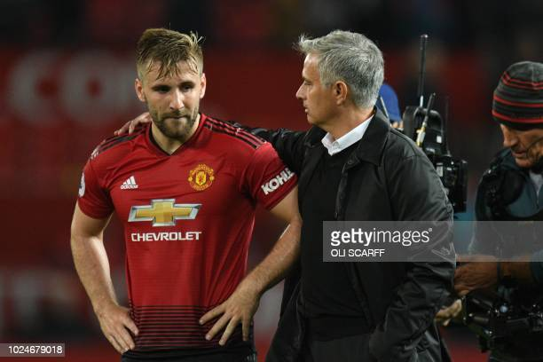 Manchester United's Portuguese manager Jose Mourinho greets Manchester United's English defender Luke Shaw after the final whistle in the English...