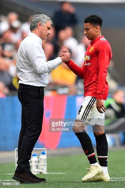 Manchester United's Portuguese manager Jose Mourinho greets Manchester United's English midfielder Jesse Lingard as he comes off the field during the...