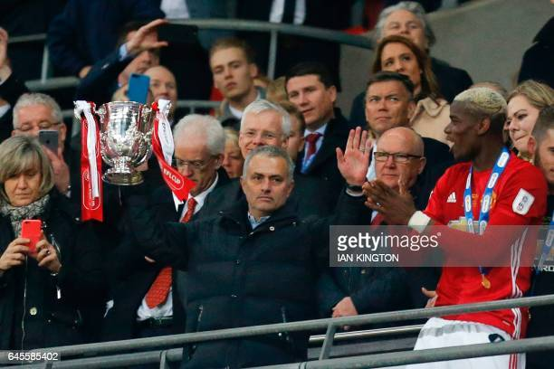 TOPSHOT Manchester United's Portuguese manager Jose Mourinho holds up the trophy as Manchester United players celebrate their victory after the...