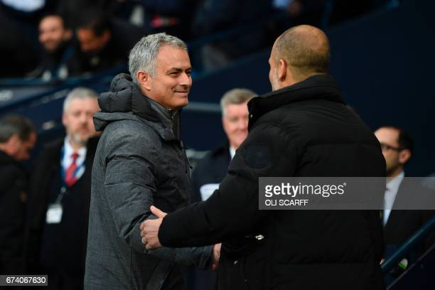 Manchester United's Portuguese manager Jose Mourinho is greeted by Manchester City's Spanish manager Pep Guardiola as they arrive for the English...