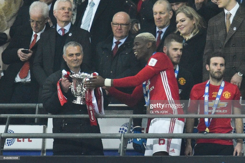 Manchester United's Portuguese manager Jose Mourinho (L) is handed the trophy by Manchester United's French midfielder Paul Pogba as Manchester United players celebrate their victory after the English League Cup final football match between Manchester United and Southampton at Wembley stadium in north London on February 26, 2017. Zlatan Ibrahimovic sealed the first major silverware of Jose Mourinho's Manchester United reign and broke Southampton's hearts as the Swedish star's late goal clinched a dramatic 3-2 victory in Sunday's League Cup final. / AFP / Glyn KIRK / RESTRICTED TO EDITORIAL USE. No use with unauthorized audio, video, data, fixture lists, club/league logos or 'live' services. Online in-match use limited to 75 images, no video emulation. No use in betting, games or single club/league/player publications. /