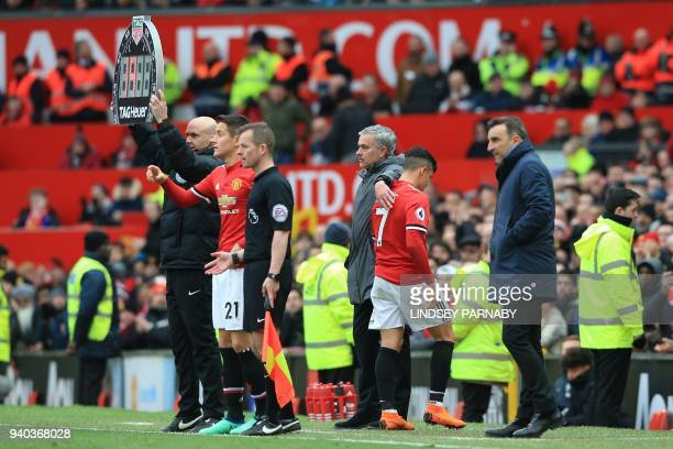 Manchester United's Portuguese manager Jose Mourinho pats Manchester United's Chilean striker Alexis Sanchez as he is substituted by Manchester...