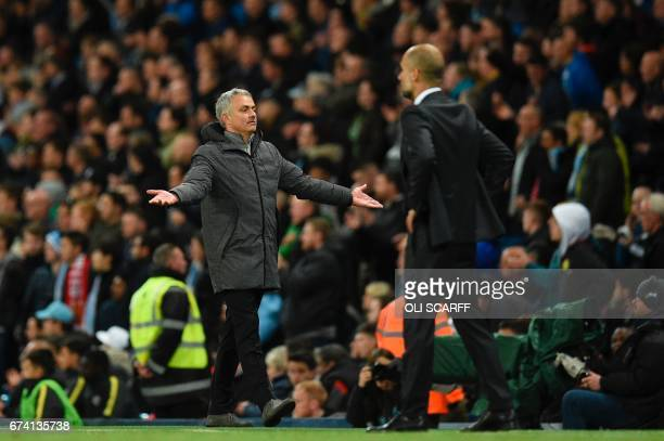Manchester United's Portuguese manager Jose Mourinho reacts on the touchline next to Manchester City's Spanish manager Pep Guardiola during the...