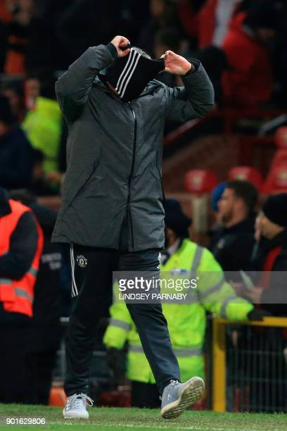 Manchester United's Portuguese manager Jose Mourinho removes his snood at the end of the English FA Cup third round football match between Manchester...