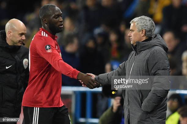 Manchester United's Portuguese manager Jose Mourinho shakes hands with Manchester United's Belgian striker Romelu Lukaku as he's substituted during...