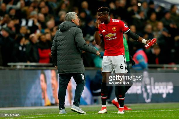 Manchester United's Portuguese manager Jose Mourinho talks with Manchester United's French midfielder Paul Pogba after the second Tottenham goal goes...
