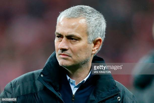 Manchester United's Portuguese manager Jose Mourinho watches the celebrations on the pitch after their victory in the English League Cup final...