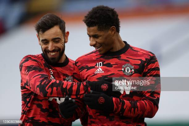Manchester United's Portuguese midfielder Bruno Fernandes and Manchester United's English striker Marcus Rashford share a joke as they warm up ahead...