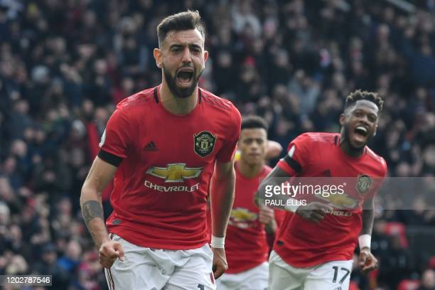Manchester United's Portuguese midfielder Bruno Fernandes celebrates scoring the opening goal from the penalty spot during the English Premier League...