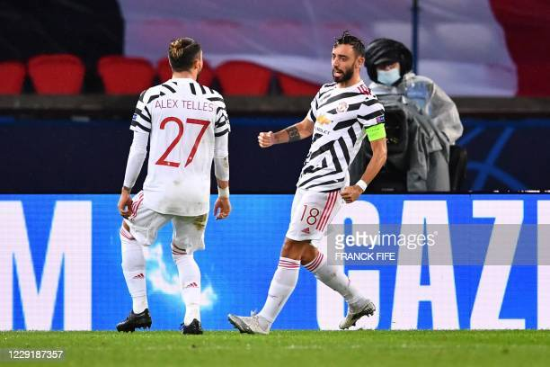 Manchester United's Portuguese midfielder Bruno Fernandes celebrates with Manchester United's Brazilian defender Alex Telles after scoring a penalty...