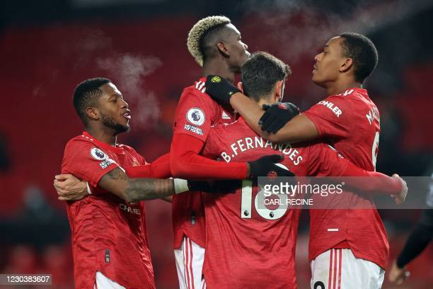 Manchester United's Portuguese midfielder Bruno Fernandes celebrates with teammates after scoring their second goal from the penalty spot during the...