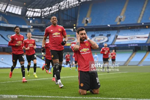 Manchester United's Portuguese midfielder Bruno Fernandes celebrates with teammates after scoring the opening goal from the penalty spot during the...