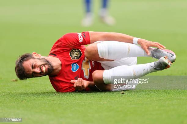 Manchester United's Portuguese midfielder Bruno Fernandes goes down after a knock during the English Premier League football match between Leicester...