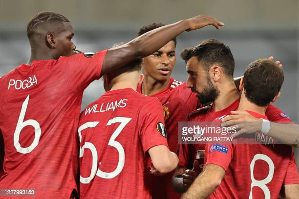 Manchester United's Portuguese midfielder Bruno Fernandes is congratulated by teammates after scoring a penalty during the UEFA Europa League...