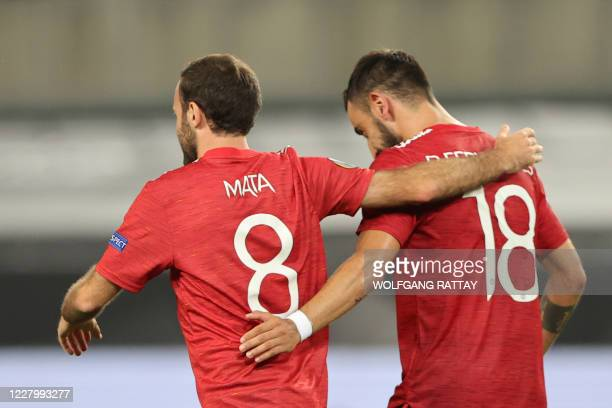 Manchester United's Portuguese midfielder Bruno Fernandes is congratulated by Manchester United's Spanish midfielder Juan Mata after scoring a...