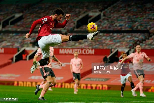 Manchester United's Portuguese midfielder Bruno Fernandes leaps to volley a cross during the English Premier League football match between Manchester...