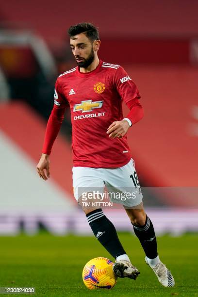 Manchester United's Portuguese midfielder Bruno Fernandes runs with the ball during the English Premier League football match between Manchester...