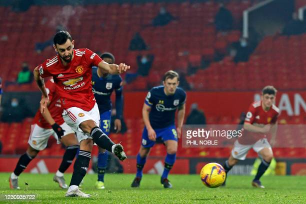 Manchester United's Portuguese midfielder Bruno Fernandes shoots to score their seventh goal from the penalty spot during the English Premier League...