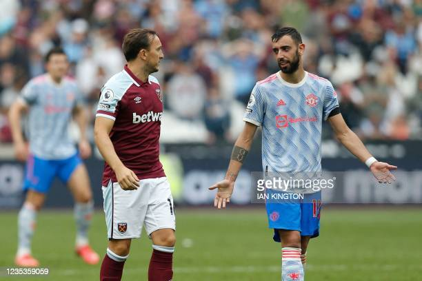 Manchester United's Portuguese midfielder Bruno Fernandes speaks with West Ham United's English midfielder Mark Noble after Noble misses a late...